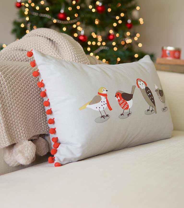 Winter birds grey cushion on sofa with pom-pom blanket and christmas tree