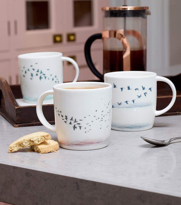 Winter skies collection featuring beautiful illustrations of a skein of geese and a starling murmuration on bone china mugs