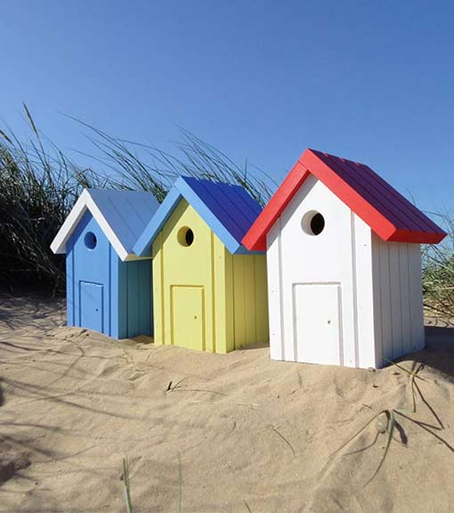 Colourful expertly designed beach hut style bird boxes for garden birds to nest in, displayed on beach
